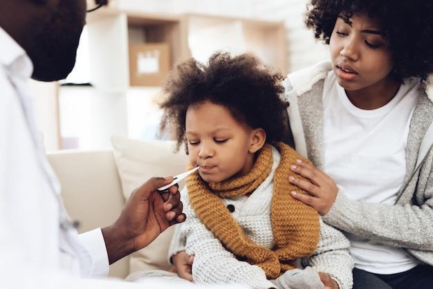 Afrikanischer doktor nimmt temperatur des kranken mädchens mit grippe.