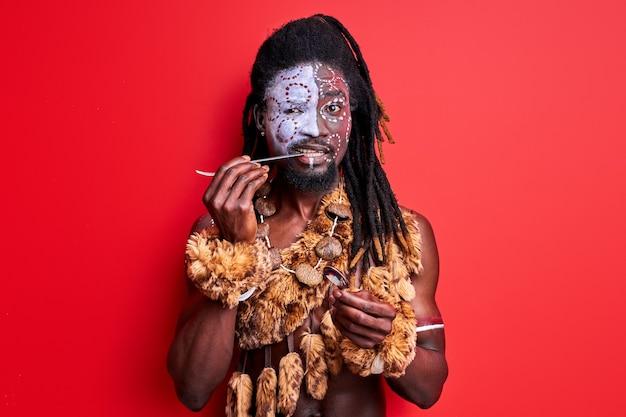 Afrikanischer eingeborener, der versucht, modernes besteck zu verwenden, löffel und gabel in händen haltend, lokalisiert über roter wand