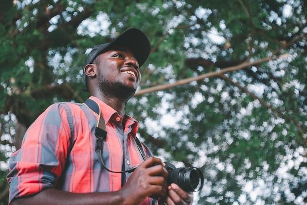 Afrikanischer fotograf, der eine kamera in der natur hält
