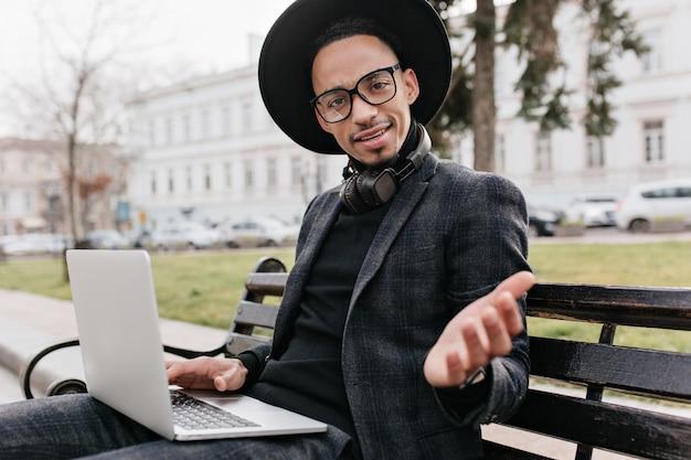 Afrikanischer freiberufler, der erstaunen ausdrückt, während er mit laptop im quadrat arbeitet. außenfoto des überraschten schwarzen mannes trägt hut, sitzt auf bank und hält computer.