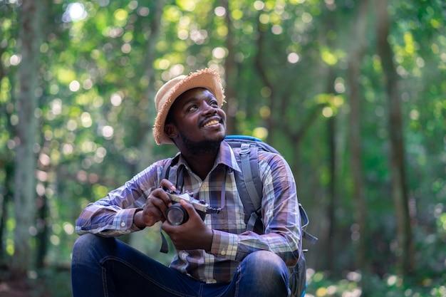 Afrikanischer freiheitsmannreisender, der kamera mit rucksack im grünen naturwald hält.