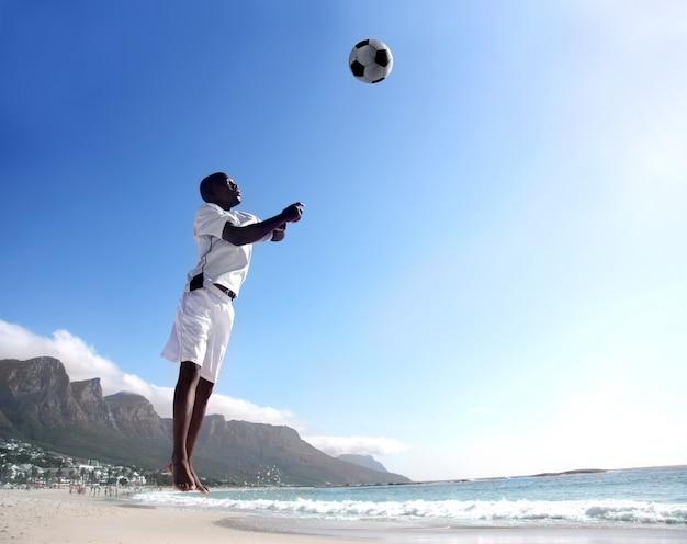 Afrikanischer fußball- oder fußballspieler, der ball auf dem strand vorangeht