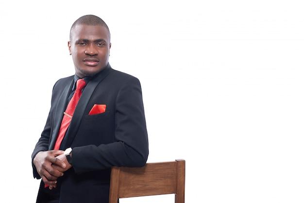 Afrikanischer geschäftsmann, der elegante schwarze suite und rote krawatte trägt, die auf stuhl stützt und hände zusammenhält.