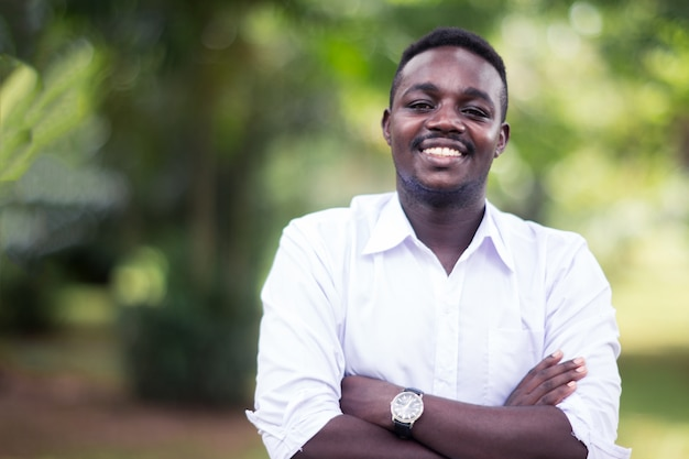 Afrikanischer geschäftsmann, der im park mit lächeln und glücklich steht