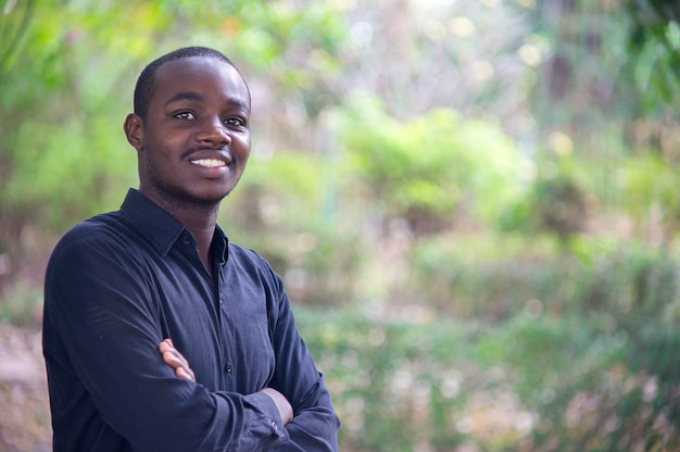 Afrikanischer geschäftsmann, der in der grünen natur schaut und lächelt.