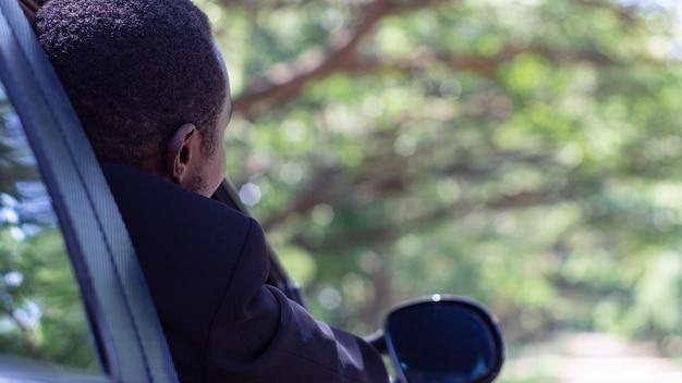 Afrikanischer geschäftsmann, der in einem auto mit offenem frontfenster fährt und sitzt. 16: 9-stil