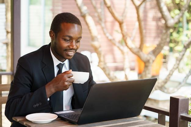 Afrikanischer geschäftsmann, der kaffee mit lächeln hält und labtop spielt.