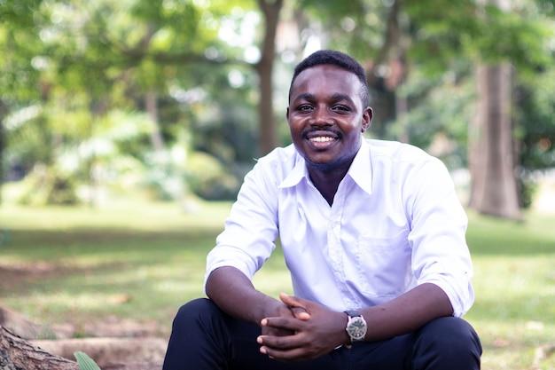 Afrikanischer geschäftsmann, der mit grünem naturhintergrund sitzt und lächelt