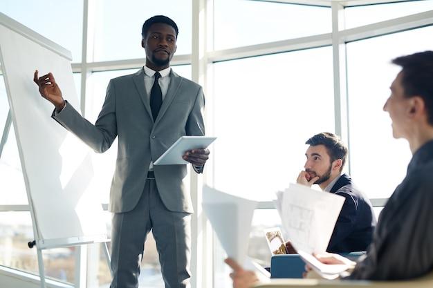 Afrikanischer geschäftsmann, der neue marketing-strategie vorlegt