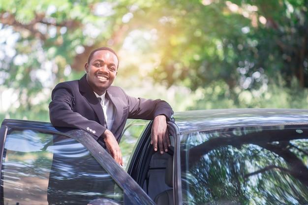Afrikanischer geschäftsmann in der klage, die nahes auto mit grünem natürlichem hintergrund steht.