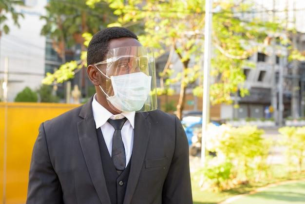 Afrikanischer geschäftsmann mit maske und gesichtsschutz, die an der bushaltestelle in der stadt draußen denken