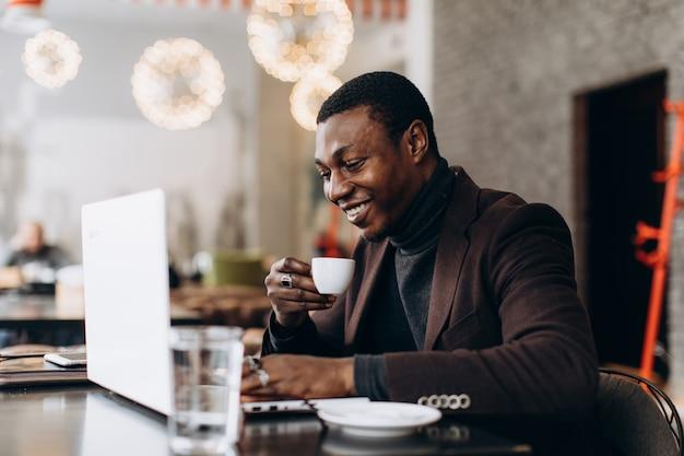 Afrikanischer geschäftsmann unter verwendung des telefons und des trinkenden kaffees beim arbeiten an laptop in einem restaurant.