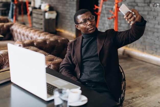 Afrikanischer geschäftsmann unter verwendung des telefons und machen selfie beim arbeiten an laptop in einem restaurant.
