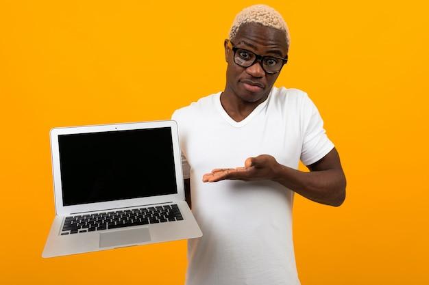 Afrikanischer geschäftsmannmann in den gläsern und im weißen t-shirt hält einen laptop mit einem modell und einem gelben studiohintergrund
