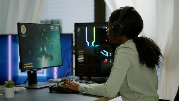 Afrikanischer glücklicher spieler, der das weltraum-shooter-spiel im gaming-heimraum gewinnt, der die hände hebt. cyber spielt auf leistungsstarken rgb-computer-streaming-videospielen mit professionellen kopfhörern für online-meisterschaften