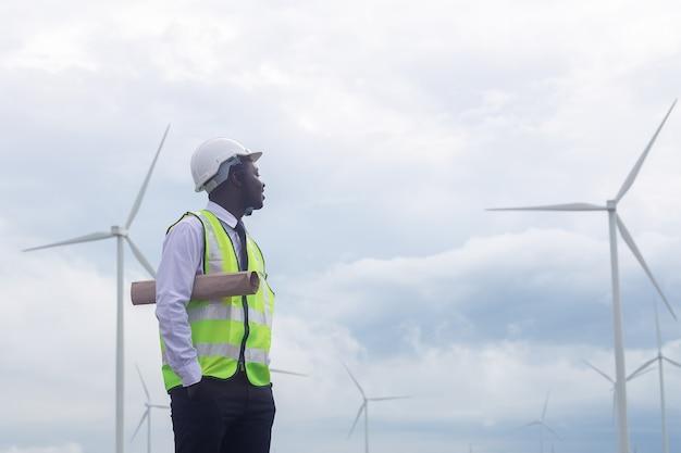 Afrikanischer ingenieur, der mit windkraftanlage steht