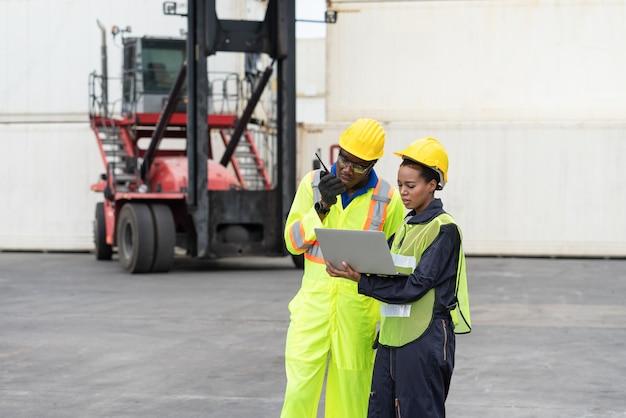Afrikanischer ingenieur mit walkie-talkie und laptop, der die beladung von containern im lager überprüft