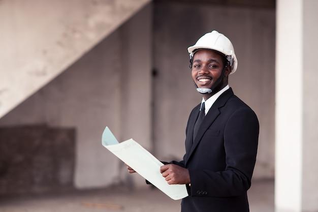 Afrikanischer ingenieurmann stehen auf und smilling
