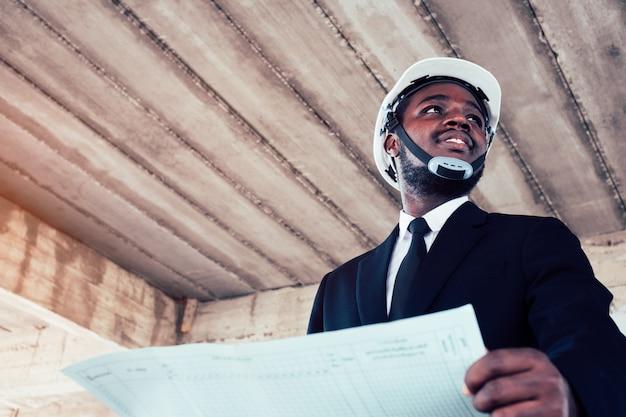 Afrikanischer ingenieurmannarchitekt, der bauvorhaben betrachtet