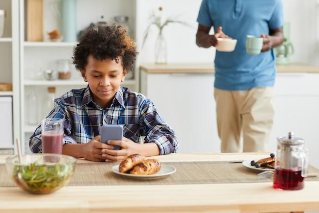 Afrikanischer junge, der am tisch sitzt und sein handy benutzt, während sein vater frühstück in der küche vorbereitet