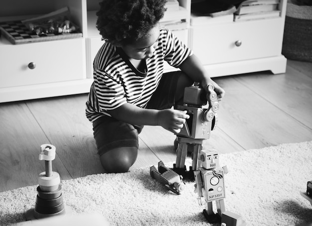 Afrikanischer junge, der zu hause mit einem roboter spielt