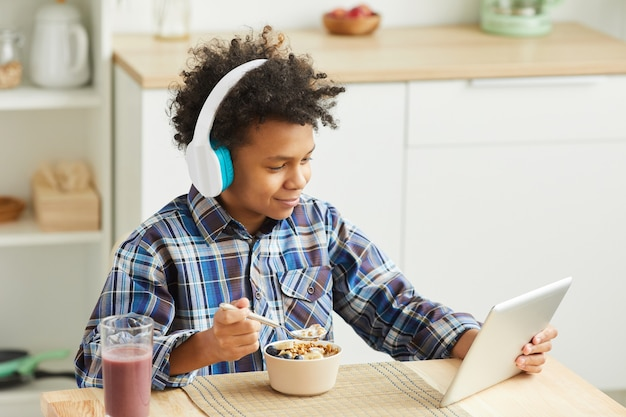 Afrikanischer junge mit lockigem haar in kopfhörern, die müsli essen und digitale tablette während des frühstücks zu hause verwenden