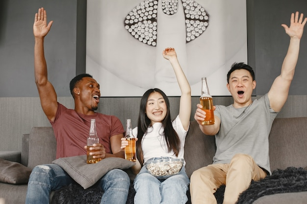 Afrikanischer junge und asiatisches paar, das fußball guckt, popcorn isst und bier trinkt. freunde, die für eine fußballmannschaft wühlen. die leute sind glücklich.