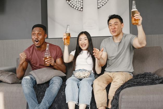 Afrikanischer junge und asiatisches paar, das fußball guckt, popcorn isst und bier trinkt. freunde, die für eine fußballmannschaft wühlen.