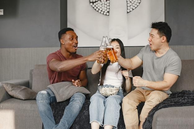 Afrikanischer junge und asiatisches paar klirren eine flasche mit einem bier freunde, die fußballspiel sehen, das popcorn isst