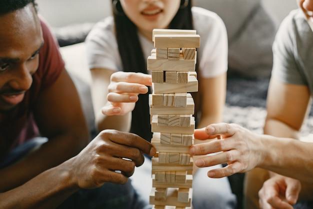 Afrikanischer junge und asiatisches paar spielen jenga spielen sie brettspiel in der freizeit konzentrieren sie sich auf ein spiel