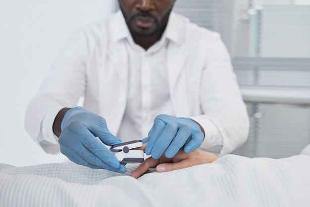 Afrikanischer junger arzt in schutzhandschuhen, der sich um seinen patienten im krankenhaus kümmert
