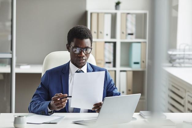 Afrikanischer junger geschäftsmann in brillen, die an seinem arbeitsplatz vor laptop sitzen und einen vertrag lesen