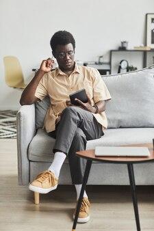 Afrikanischer junger mann, der auf dem sofa sitzt und während seiner freizeit zu hause ein digitales tablet benutzt