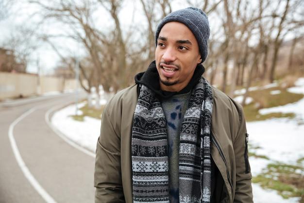 Afrikanischer junger mann, der auf der straße im winter geht