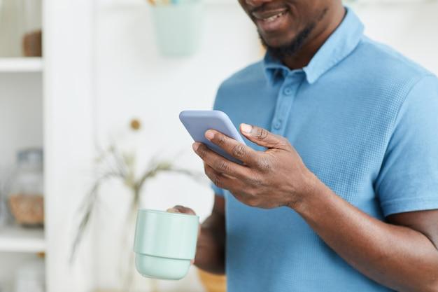 Afrikanischer junger mann, der eine nachricht auf seinem handy tippt, während er am morgen kaffee trinkt
