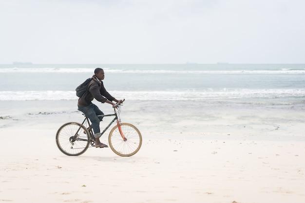 Afrikanischer junger mann, der fahrrad am tropischen strand reitet