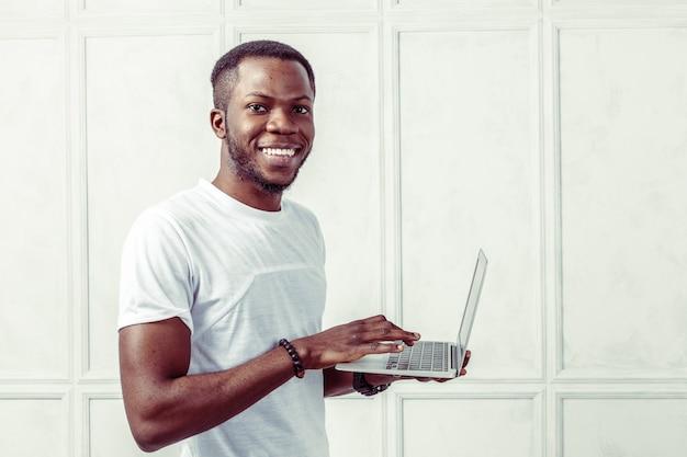 Afrikanischer junger mann, der laptop hält