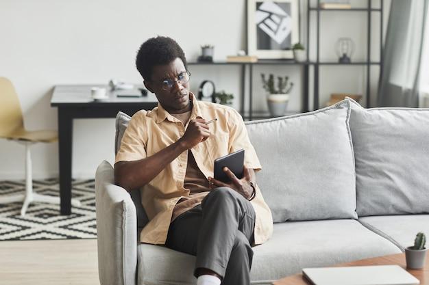 Afrikanischer junger mann, der sich auf dem sofa entspannt und etwas online auf einem digitalen tablet im zimmer zu hause ansieht