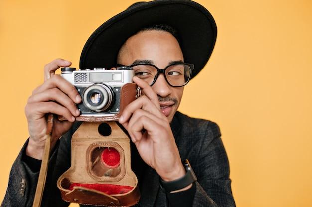 Afrikanischer junger mann, der spielerisch mit kamera auf gelber wand aufwirft. innenfoto des talentierten fotografen im eleganten hut, der spaß hat