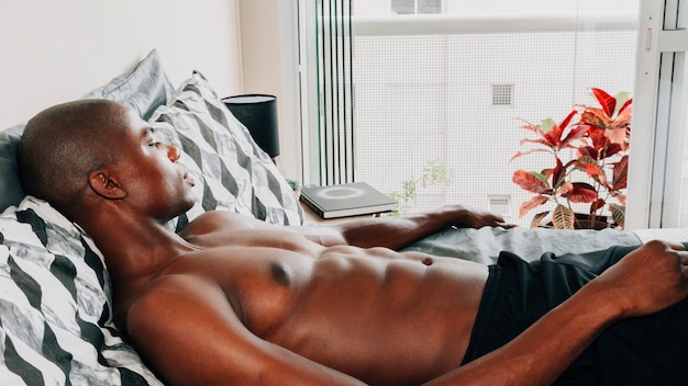 Afrikanischer junger mann des hemdlosen sitzes, der auf bett sich entspannt