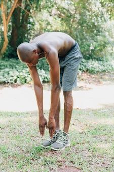 Afrikanischer junger mann des hemdlosen sitzes, der im park trainiert