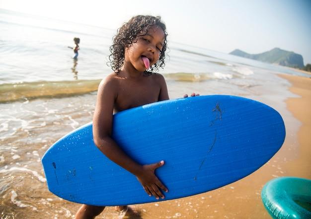 Afrikanischer kleiner junge, der am strand spielt