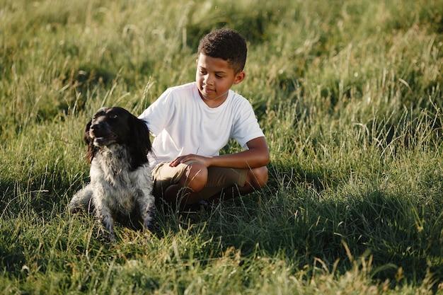 Afrikanischer kleiner junge. kind in einem sommerpark. kind spielt mit hund.