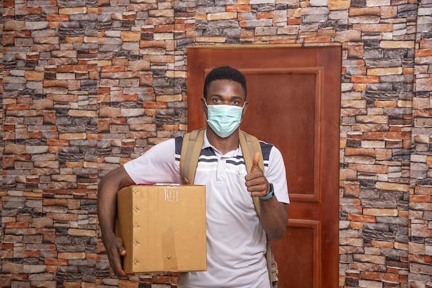 Afrikanischer kurier mit einer gesichtsmaske, die die daumen-nach-oben-geste macht, während er ein paket ausliefert - covid-19