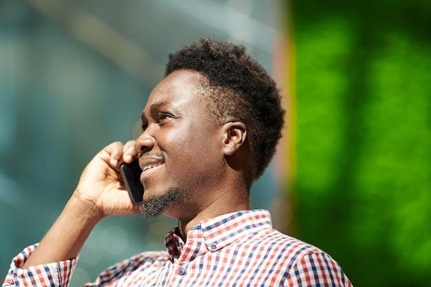 Afrikanischer lächelnder mann, der auf mobiltelefon spricht, während draußen geht