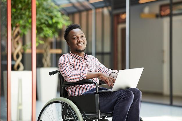 Afrikanischer lächelnder mann, der im rollstuhl sitzt und laptop-computer im einkaufszentrum verwendet