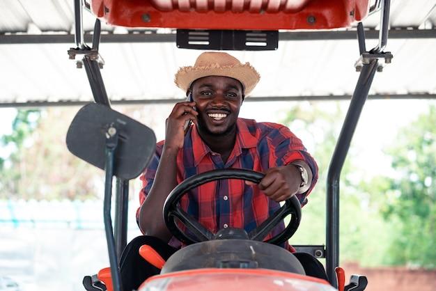 Afrikanischer landwirt, der smartphone und fahrtraktor im bauernhof während der ernte auf dem land verwendet. landwirtschafts- oder anbaukonzept