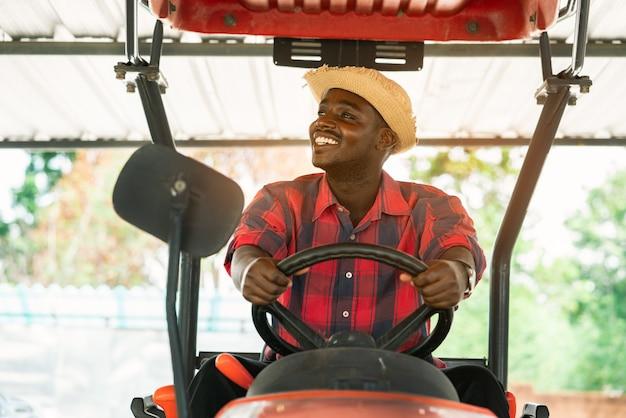 Afrikanischer landwirt, der traktor im bauernhof während der ernte auf dem land fährt. landwirtschafts- oder anbaukonzept