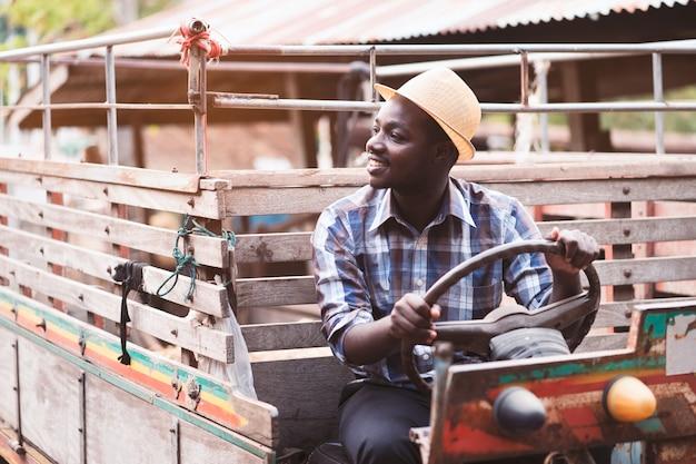 Afrikanischer landwirt fährt kleinen traktor auf die landschaft