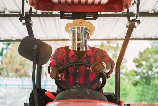Afrikanischer landwirt tragen gesichtsschutz und fahrtraktor in der farm während der ernte auf dem land. landwirtschafts- oder anbaukonzept
